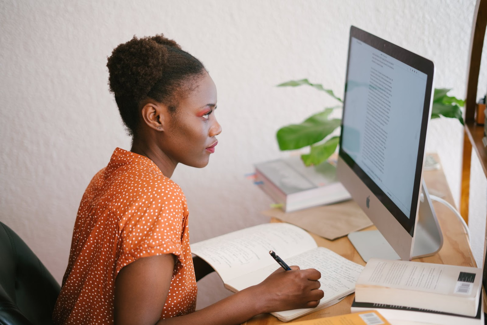A woman sitting at a desk and looking at a computer monitor while she writes in a notebook.