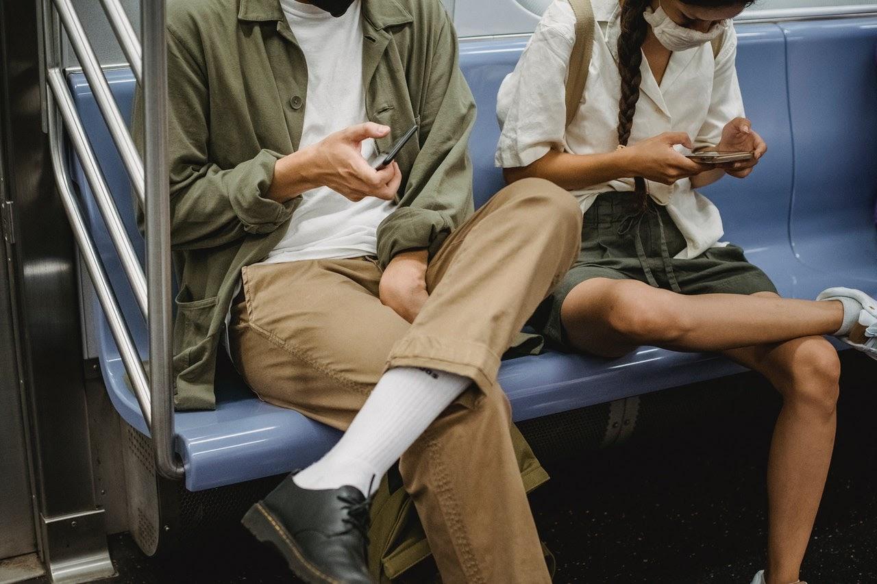 Two passengers sit cross legged on a subway.