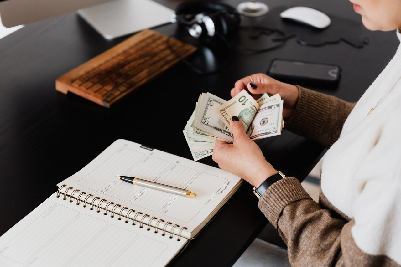 A woman counts her cash at her desk with a notebook in front of her.