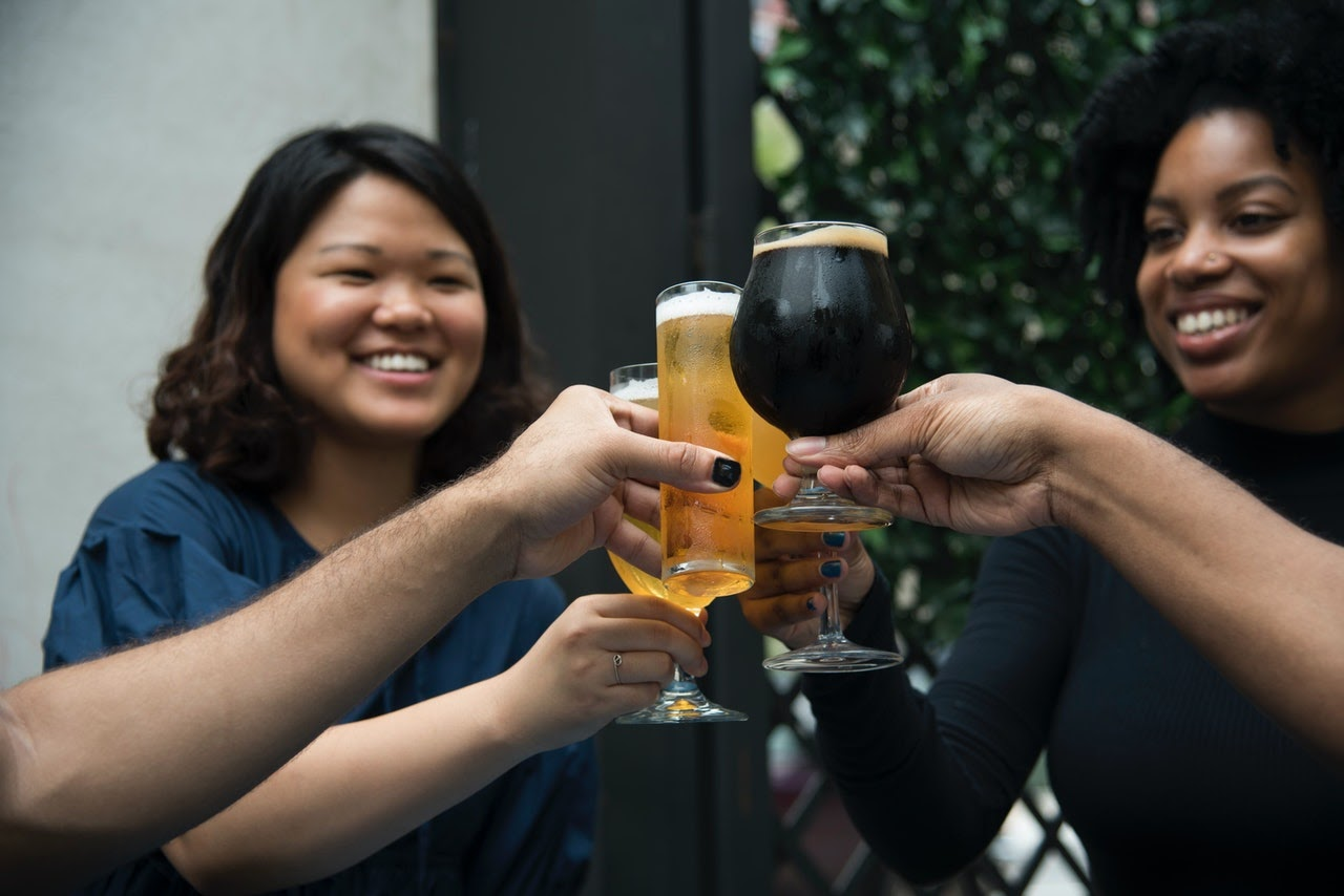 A group of ladies make a cheers with their beers.