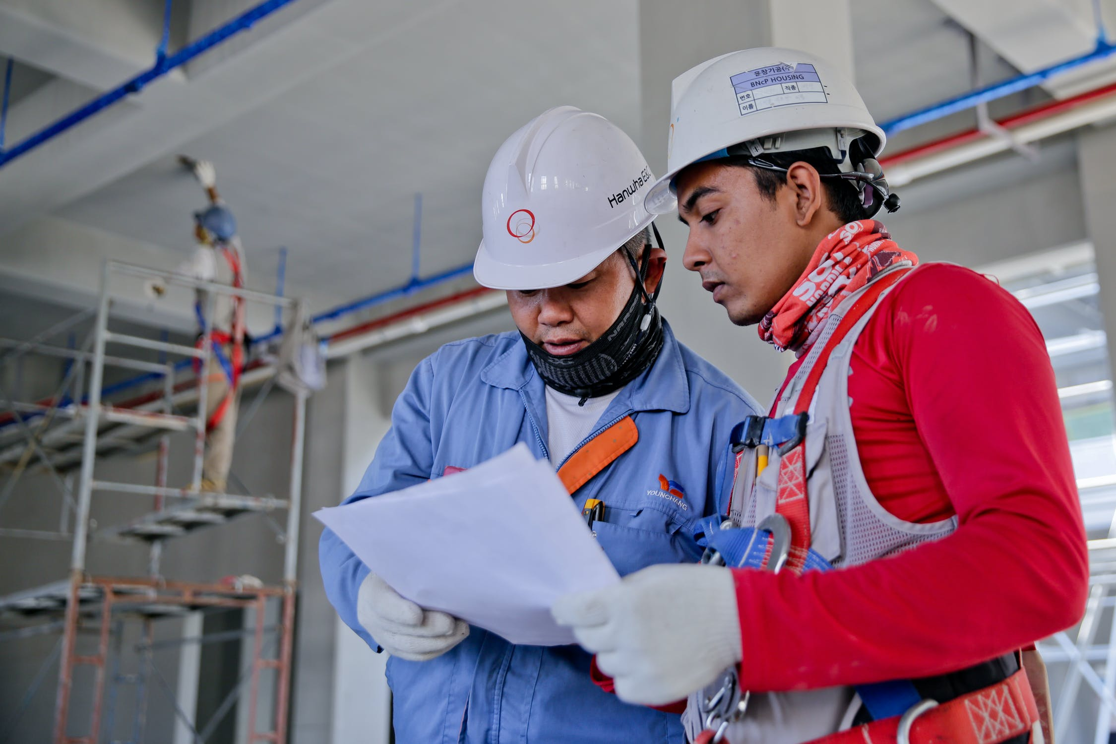 Two men in hard hats look over a blueprint together.