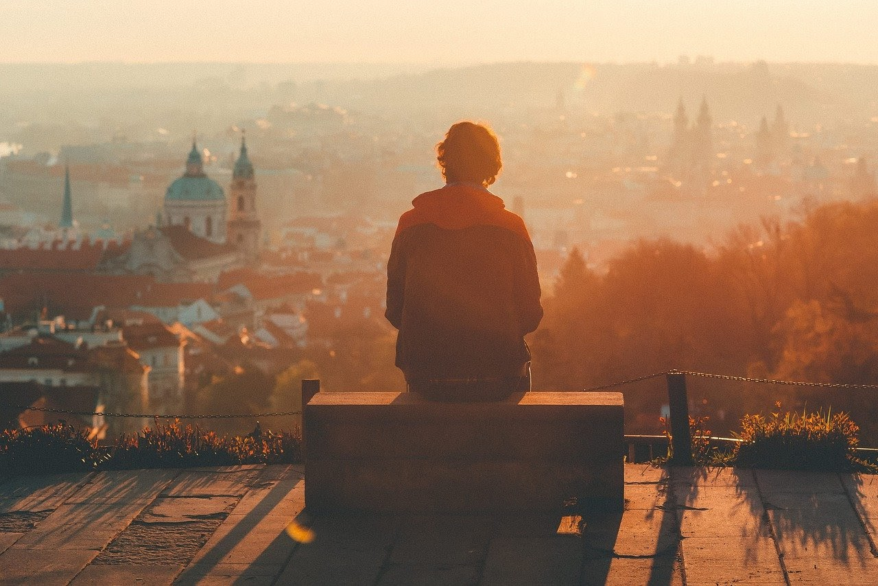 A man sits on a bench, back to the camera, on a hill overlooking the city at sunset.