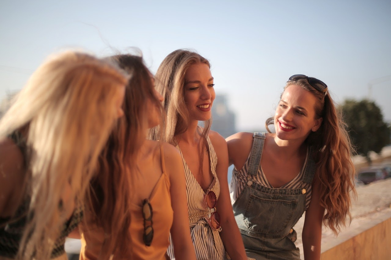 A group of four women lean against a railing talking to one another.