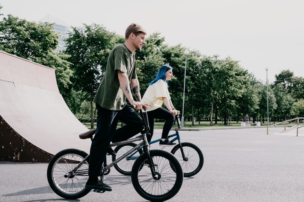 Two people, a man and a woman, are on trick bikes at a skating park.