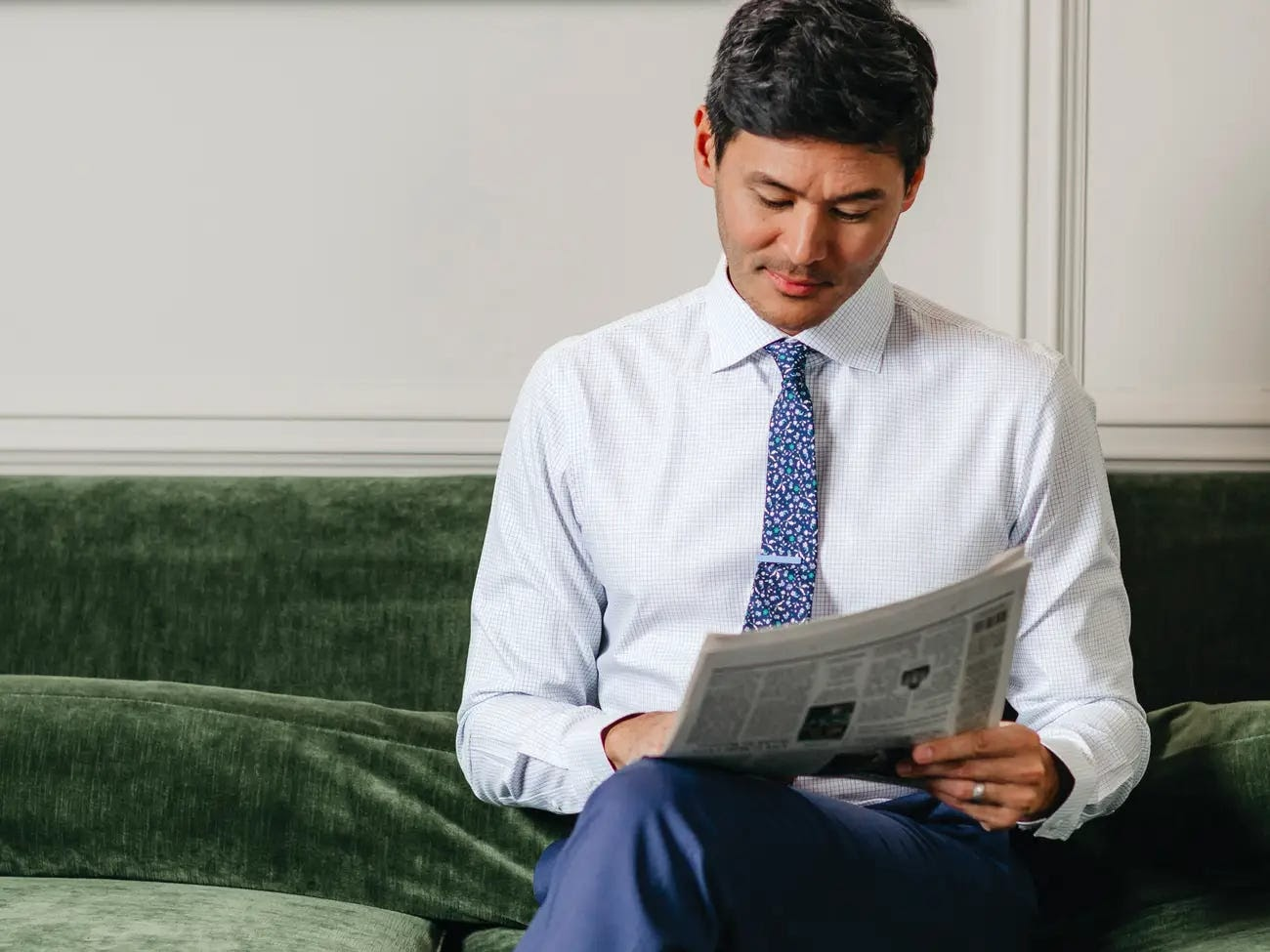 a business man in a business professional suit reads the newspaper