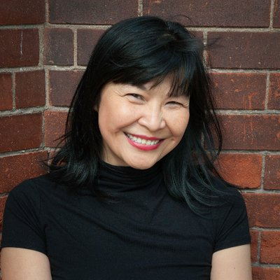 Carriane Leung smiles in front of brick wall.