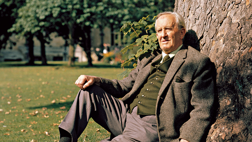 J.R.R. Tolkien relaxes with his back against a tree.