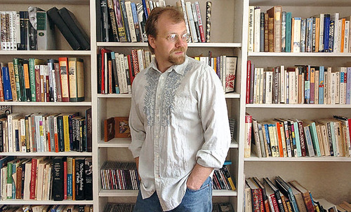 George Saunders looks away from the camera as he poses in front of a bookshelf.