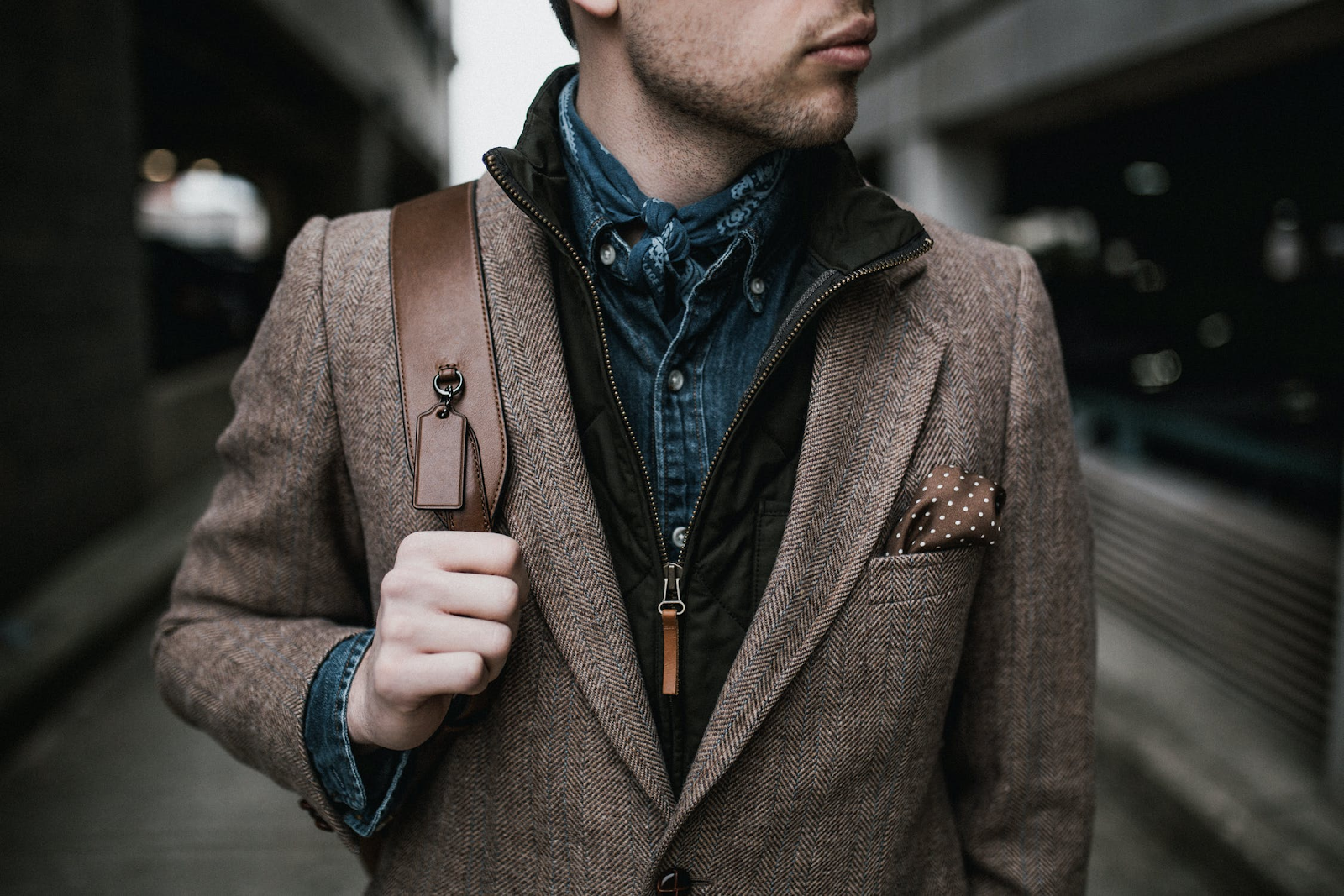 Young adult establishes his unique fashion sense with a fun pocket square and a bandana.