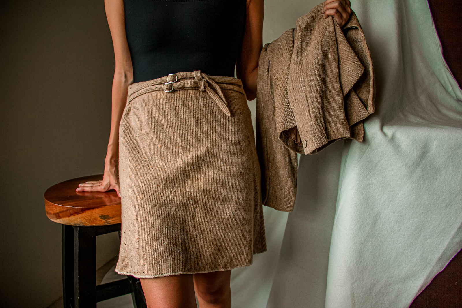 Young adult woman wears black and khaki in a business casual work outfit.
