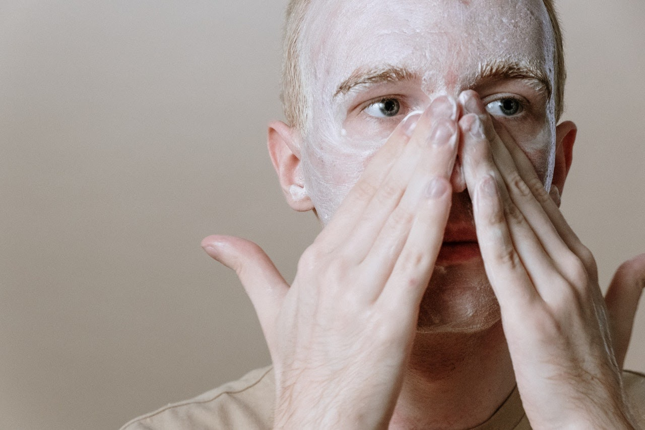 A man washes his face with white cleanser cream.