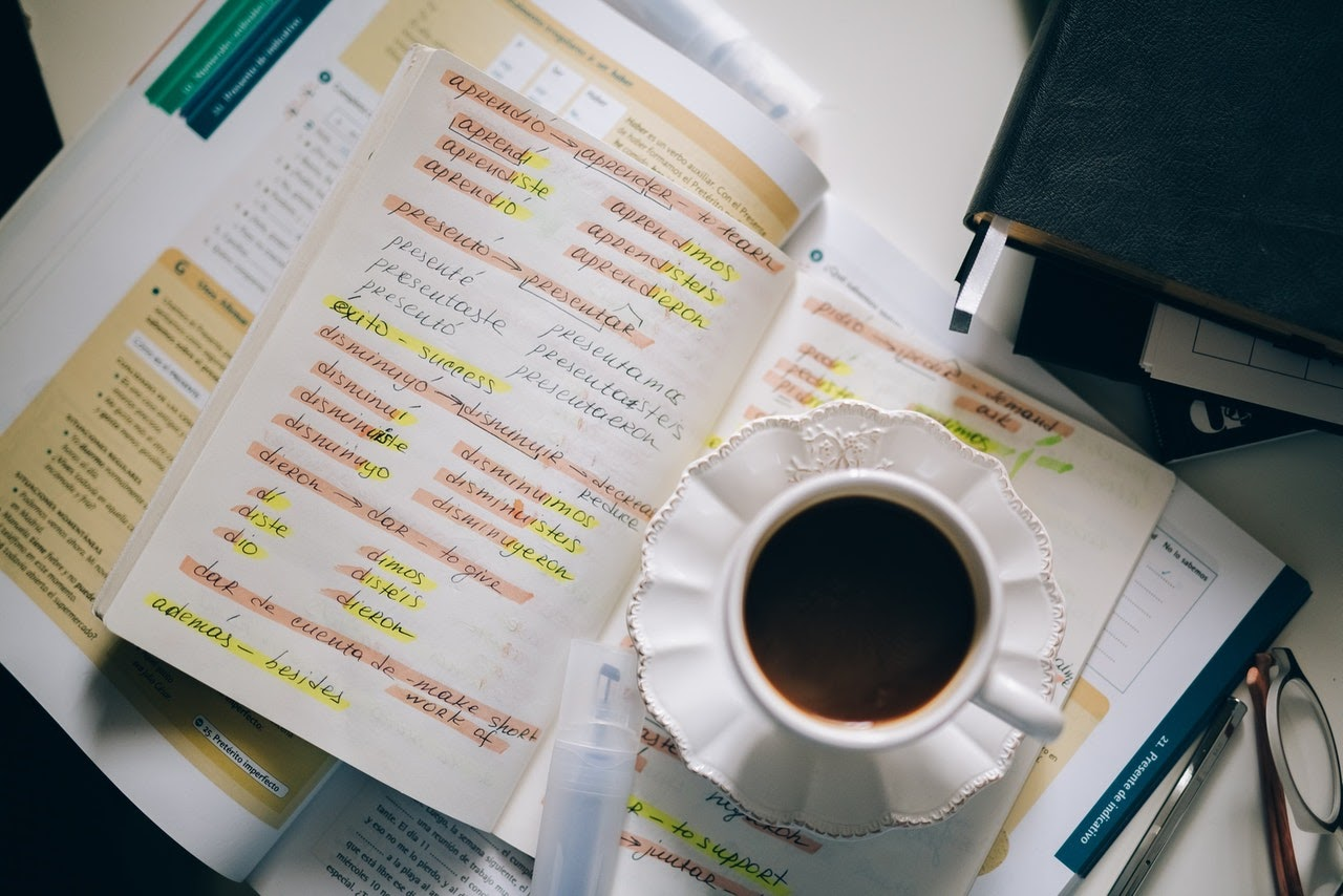 An open book on a desk with highlighted Spanish vocabulary sits under a cup of coffee.