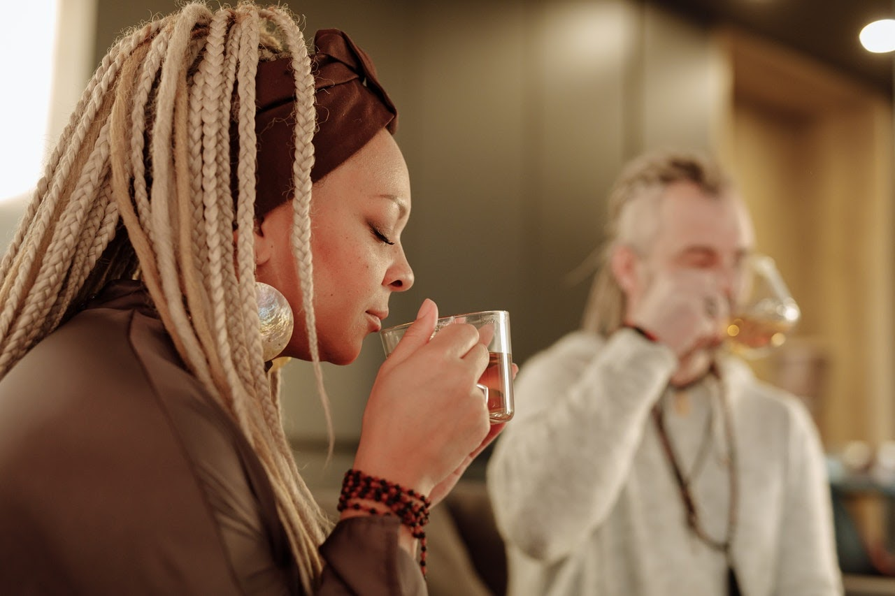 A woman drinks a cup of tea, her braids tied back with a red bandana.