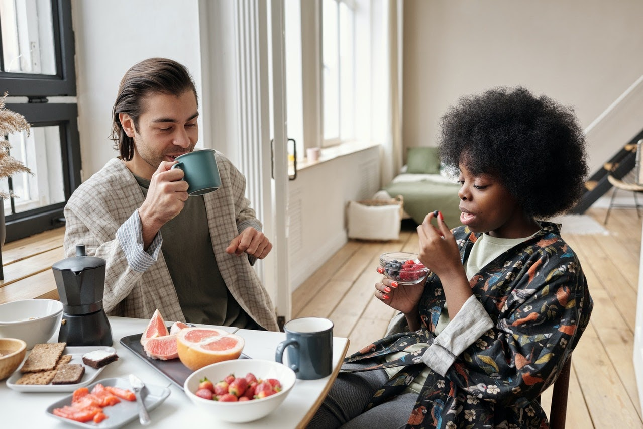 A man and a woman sit at a table eating a breakfast of fruit and toast.