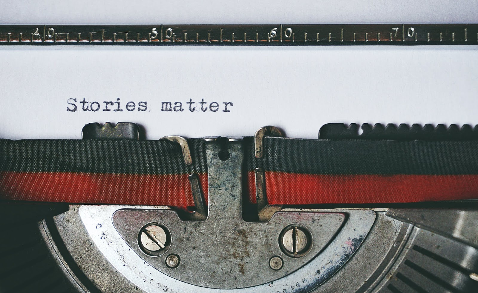 """A typewriter writing the words """"stories matter"""" on a blank white page."""
