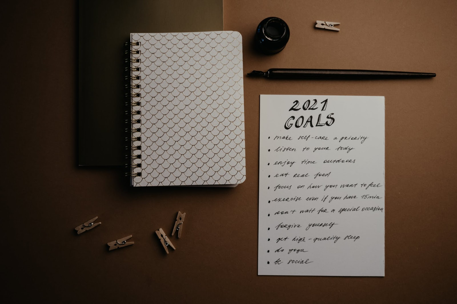 A list of goals for 2021 written on a piece of paper that is lying on a desk next to a journal and a fountain pen.
