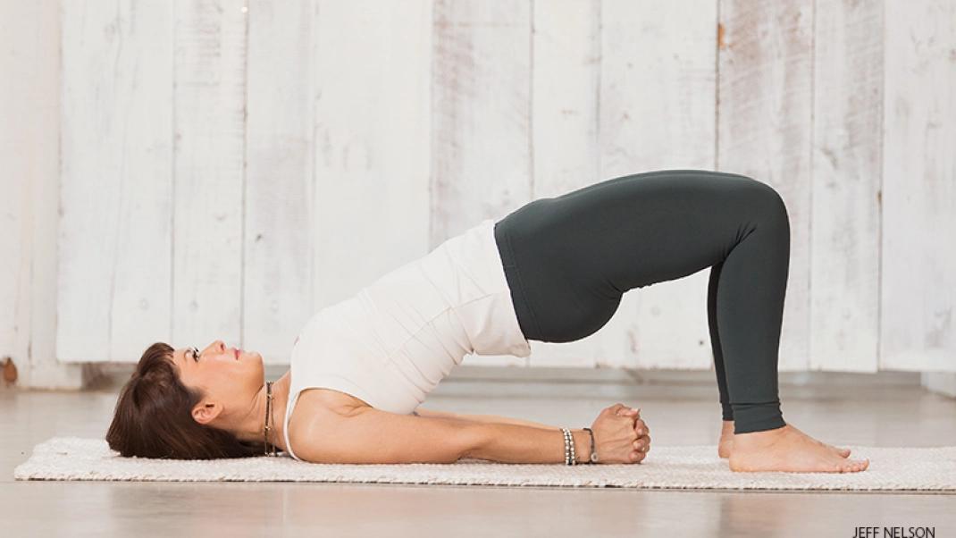 A woman practicing bridge pose