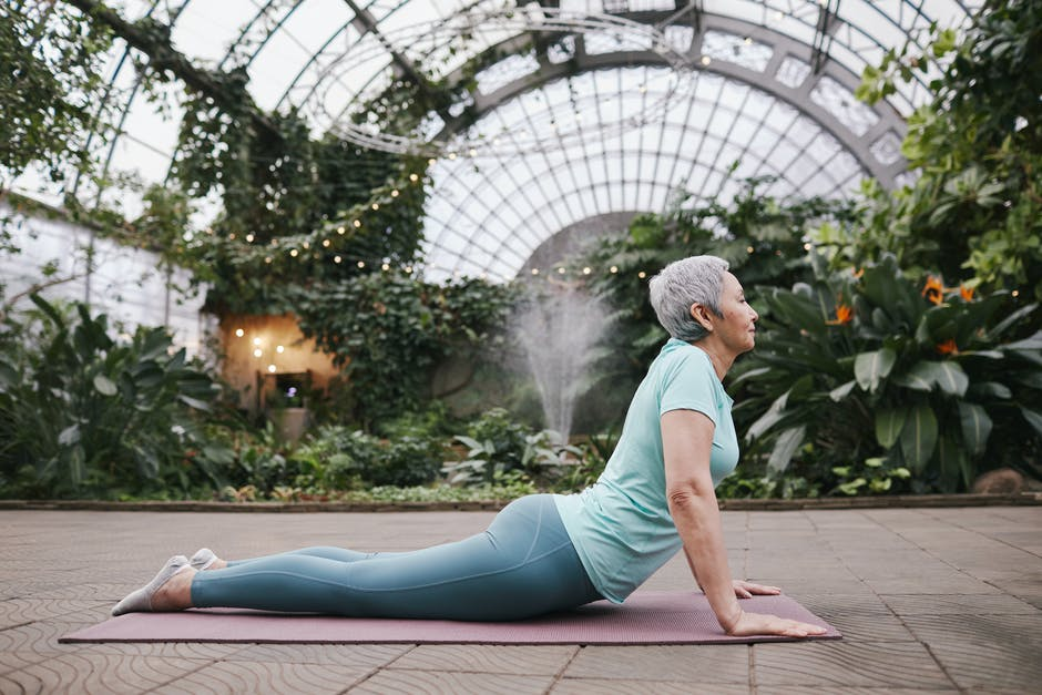 practicing cobra pose in a conservatory garden