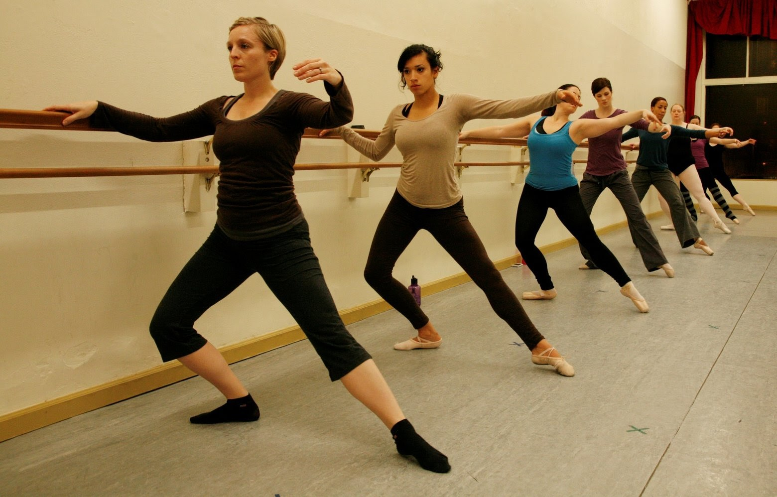 A group of ballet students dancing at a barre.