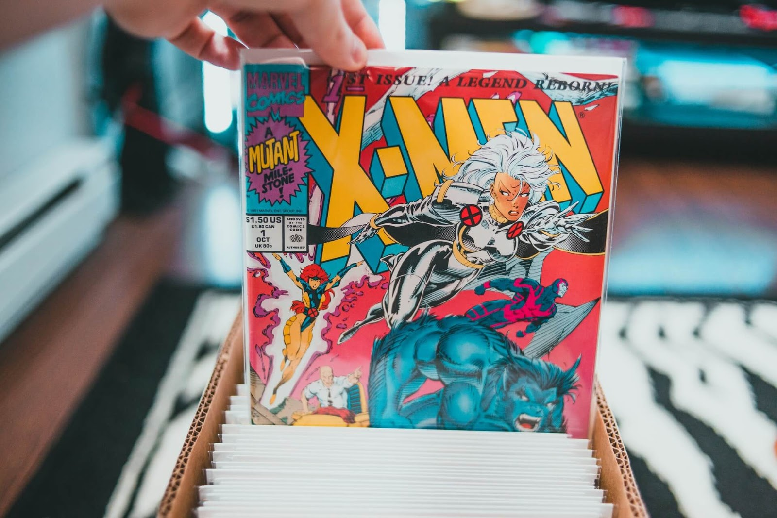 A person holds an x-men comic in their hand with Storm on the front.