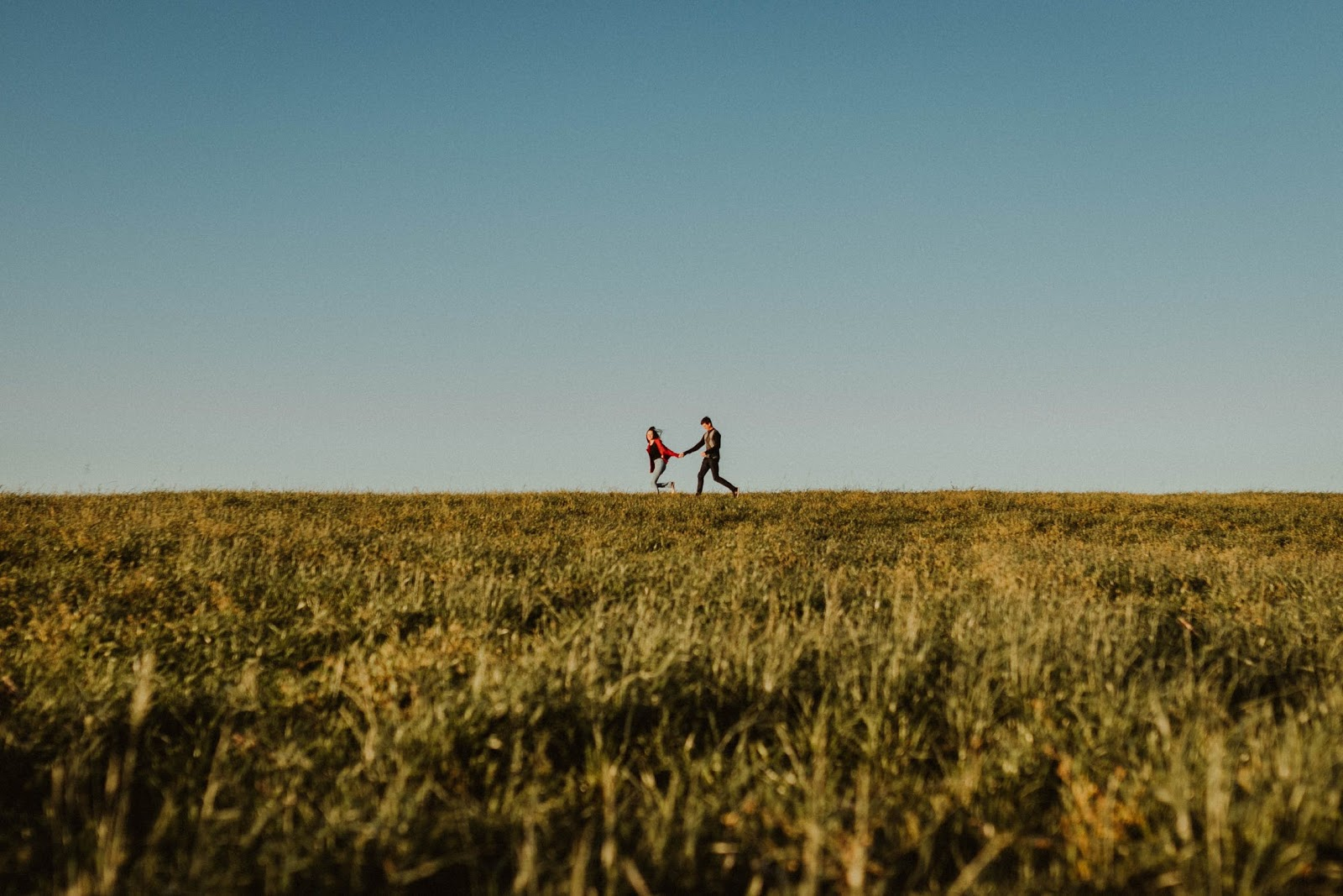 A young couple on a date holding hands and running through an open meadow.