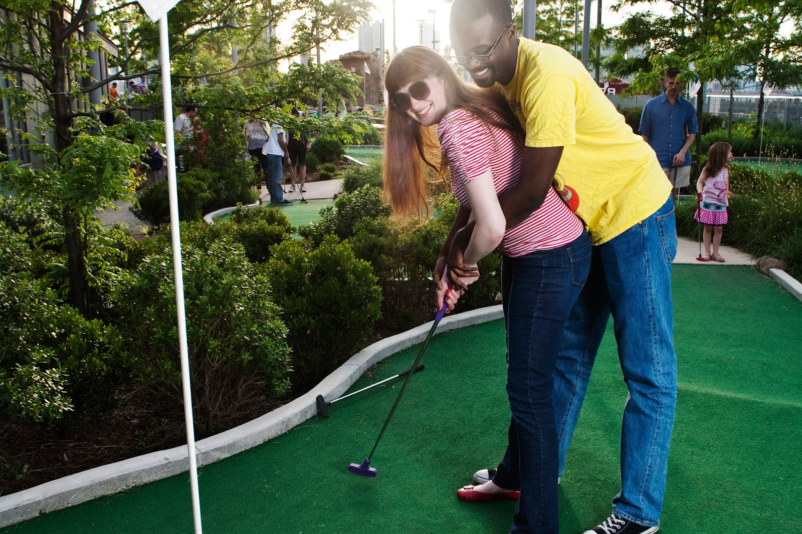 A couple on a mini golf course hold a putter together and hit a golf ball.