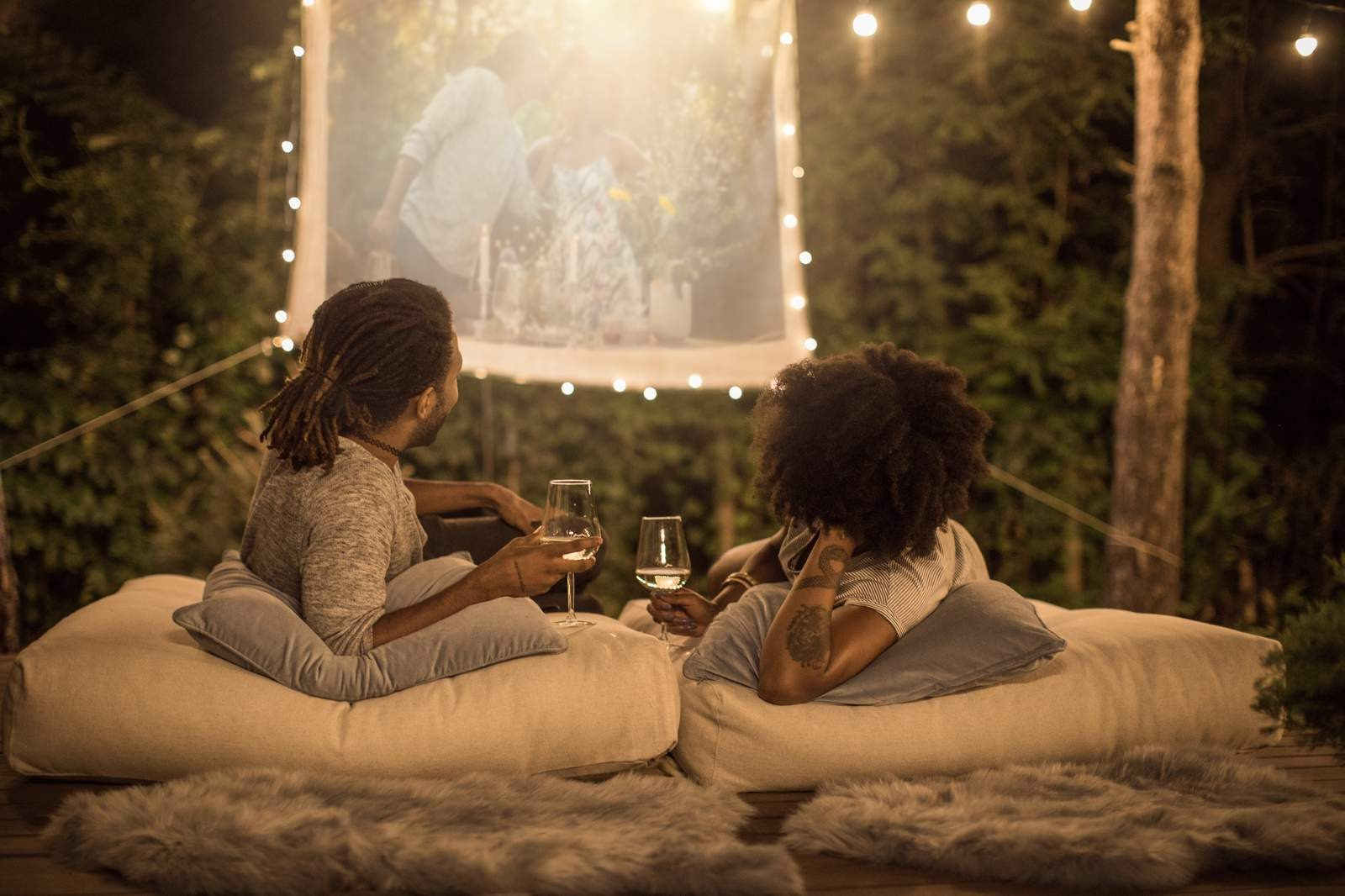 A couple on a date drinking wine and watching a movie outdoors.