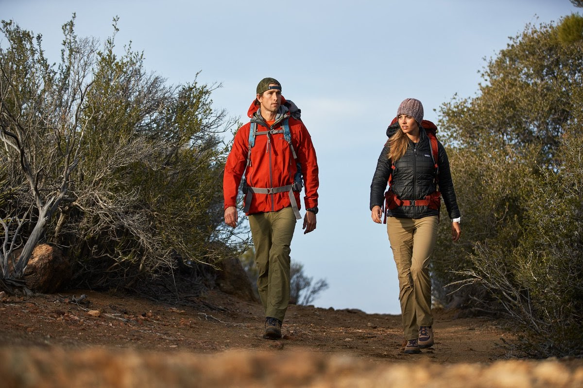 A man and woman on a date walk on a hiking trail.