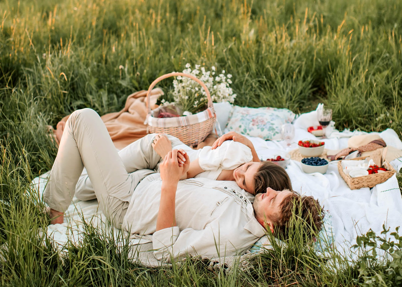 A couple lays on a blanket and looks at the sky while enjoying a picnic together.