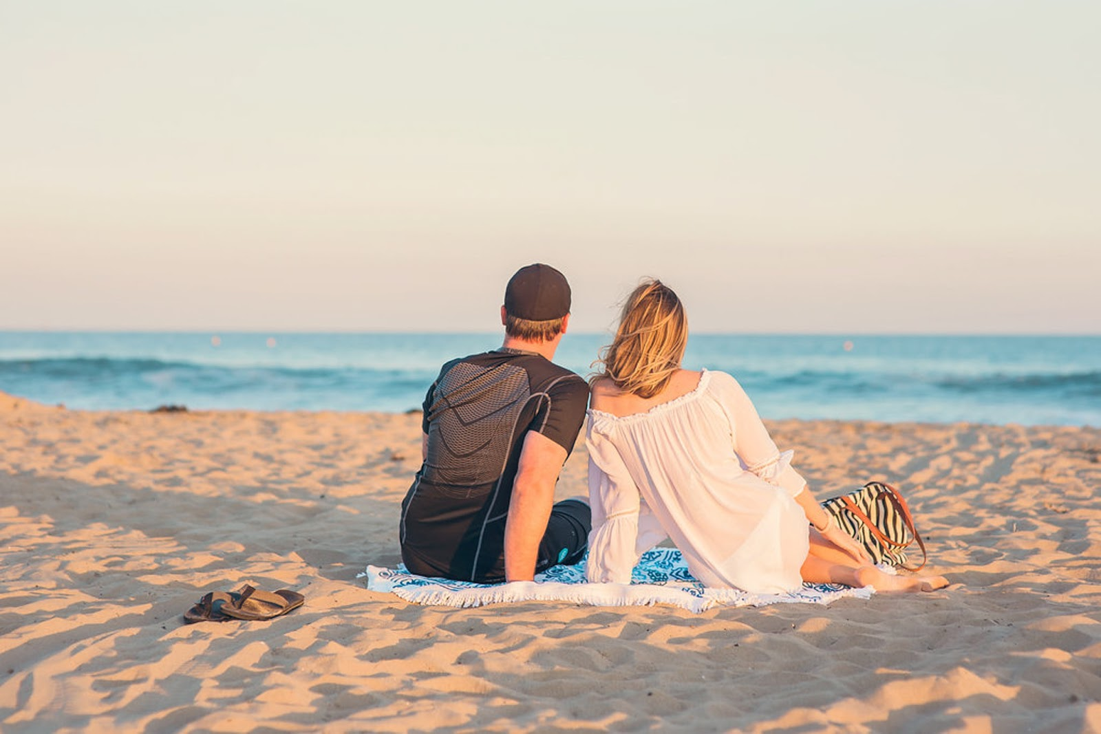 A man and woman sit on a sandy beach and look at ocean waves.
