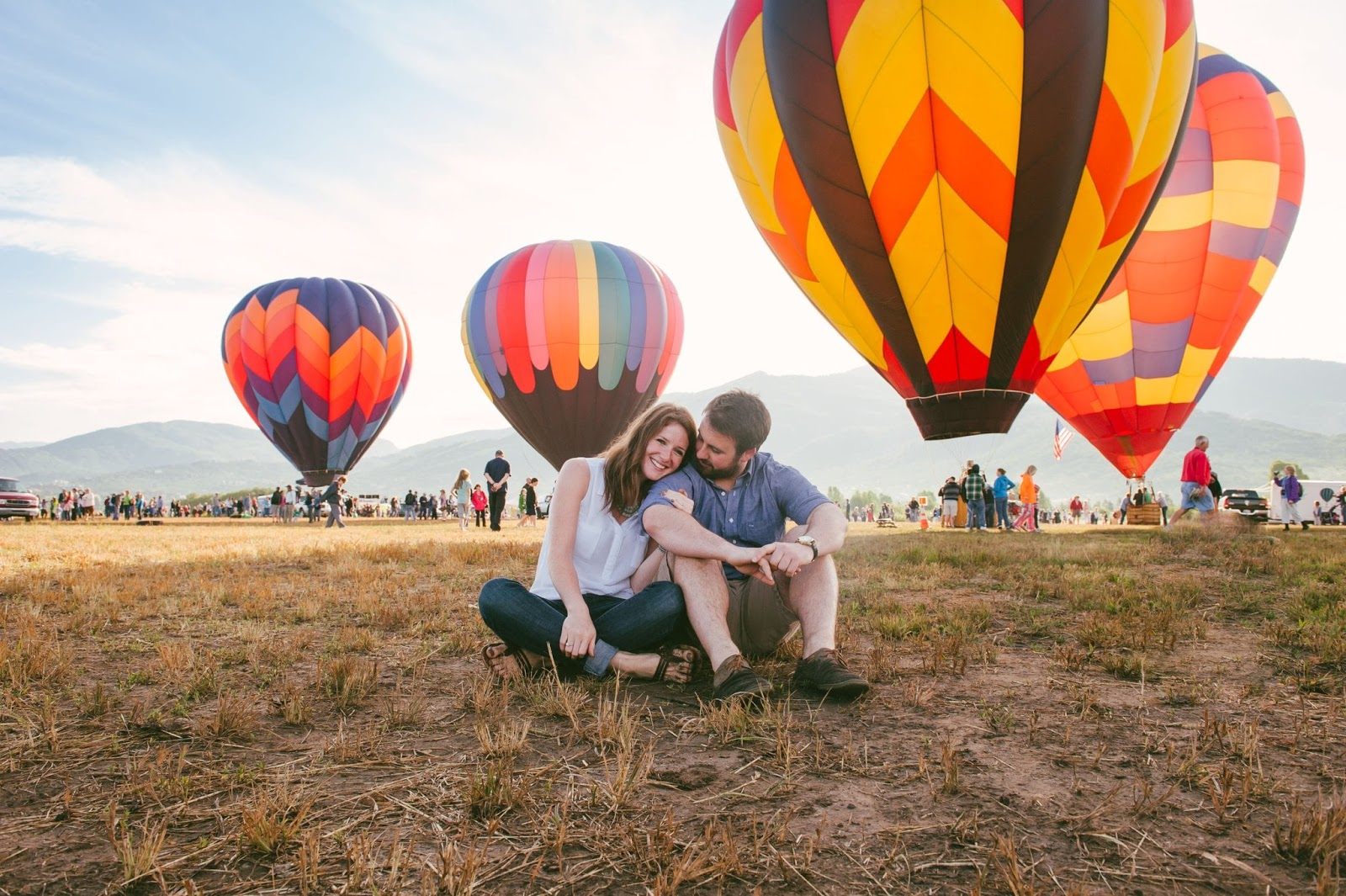 A couple sit on a grassy open field and watch hot air balloons take off from the ground.