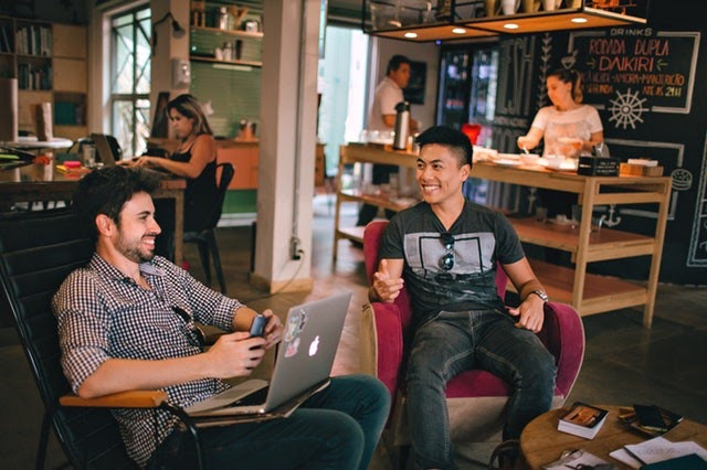 two men chat while working remotely together