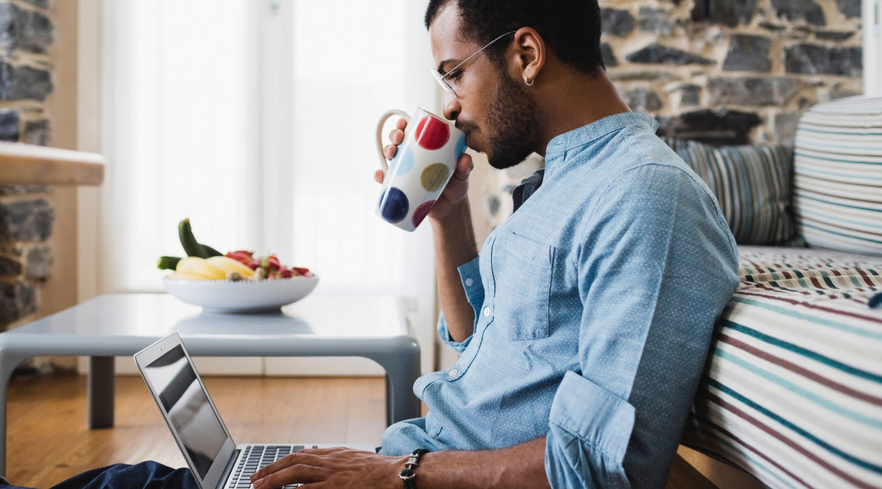 a man sips his coffee while relaxing in his at home work space
