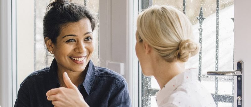 two female coworkers chat at work