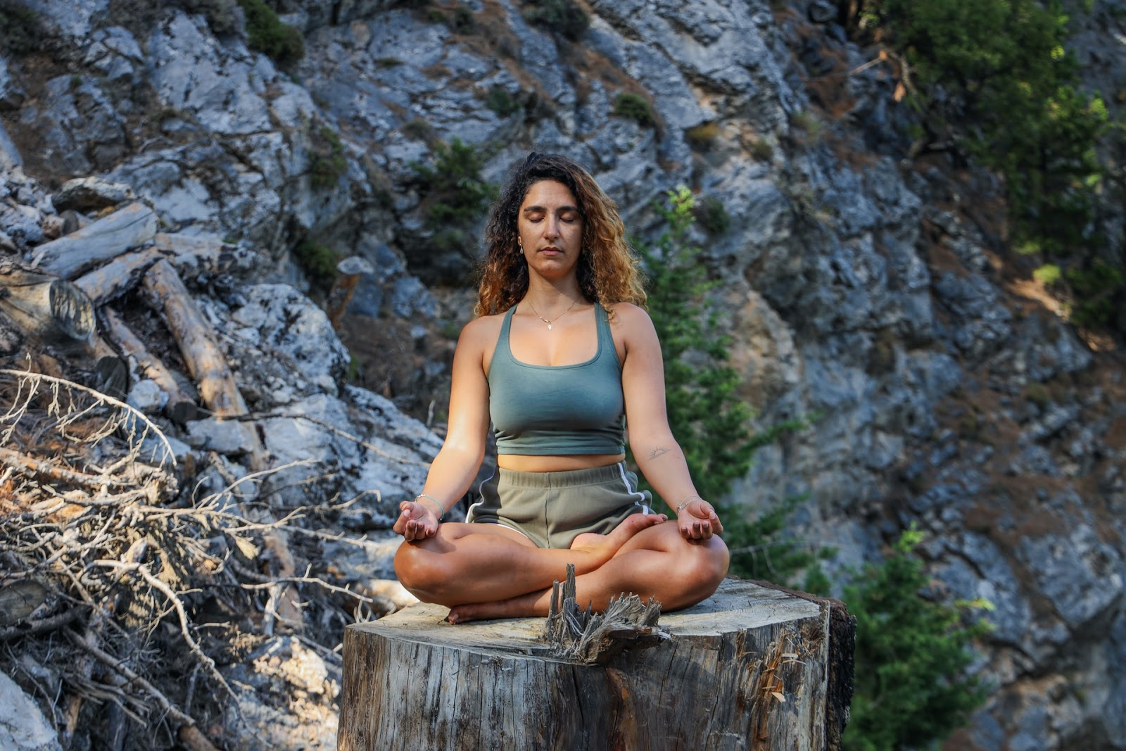 woman meditating on a tree stump in the forest
