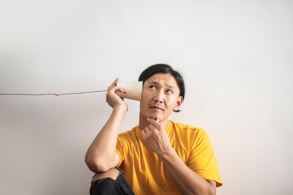 A man listening through a string and paper cup phone