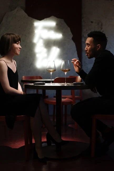 two people sharing a glass of wine at dinner