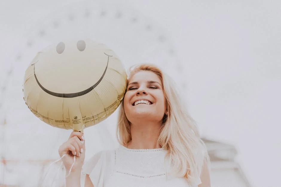 Smiling woman holding a smiley face balloon