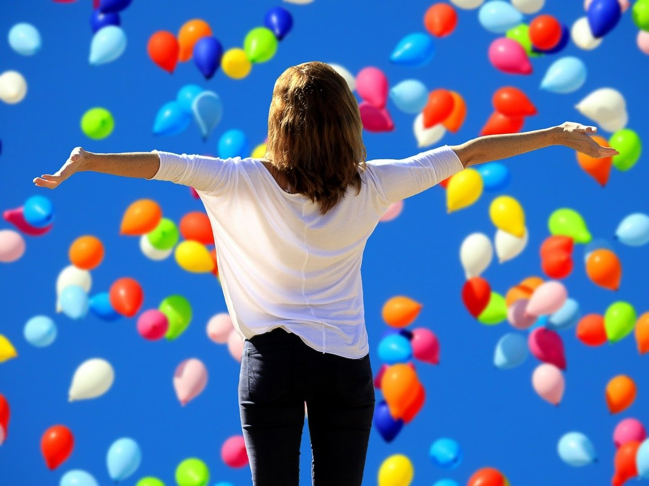 a woman celebrates her relationship with herself surrounded by balloons