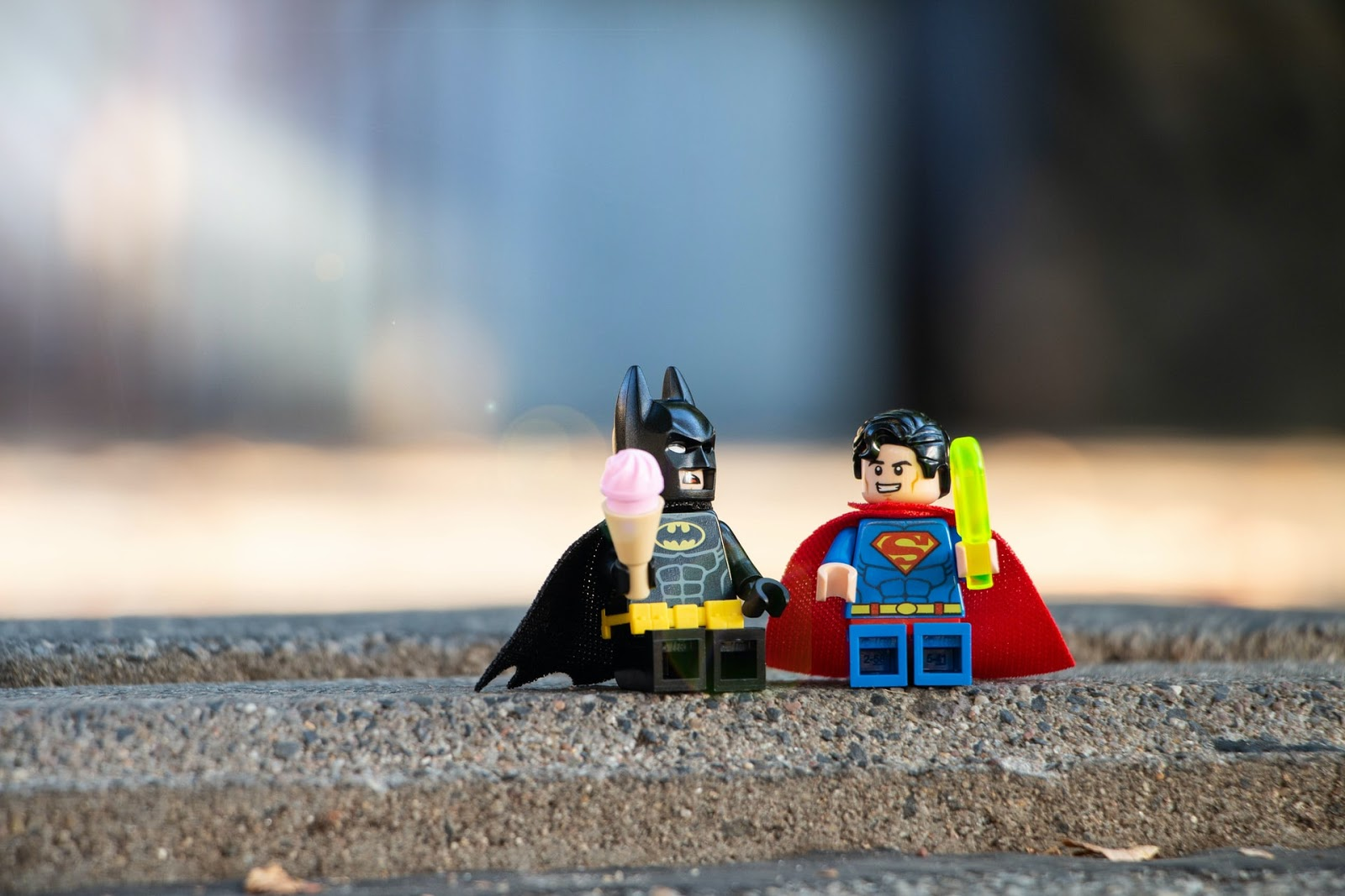 A lego batman and superman, each holding an ice cream cone, sit on a sidewalk.