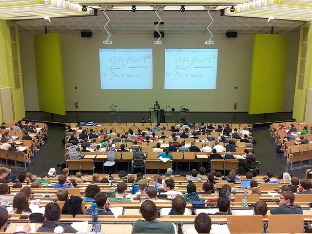 a class sits in a large lecture hall