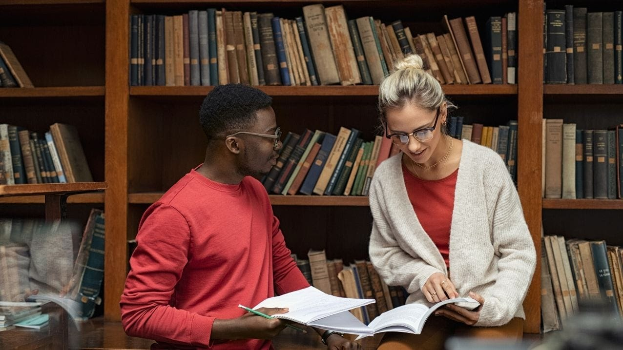 two friends study together in the college library