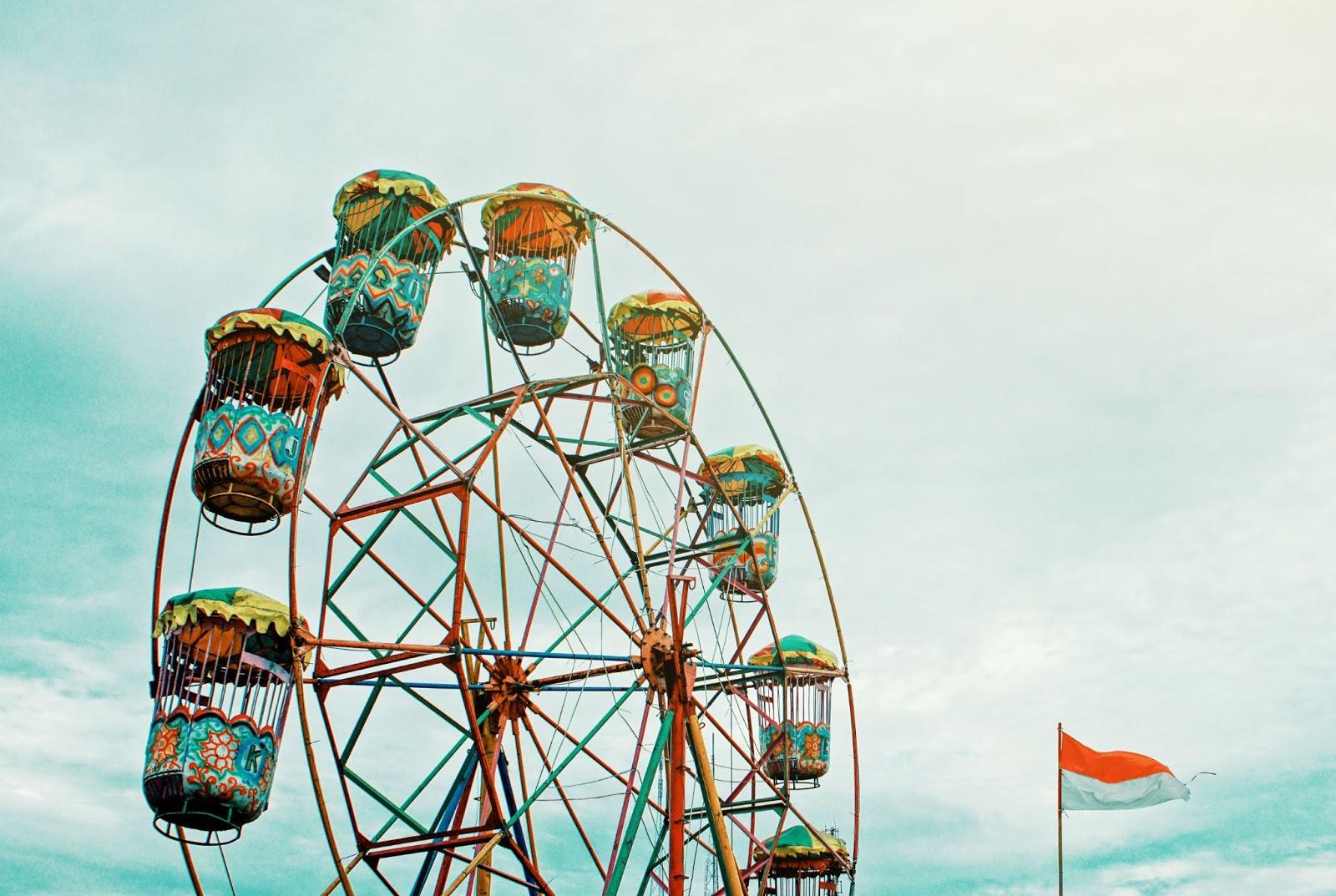 Colorful ferris wheel against a cloudy summerday sky.