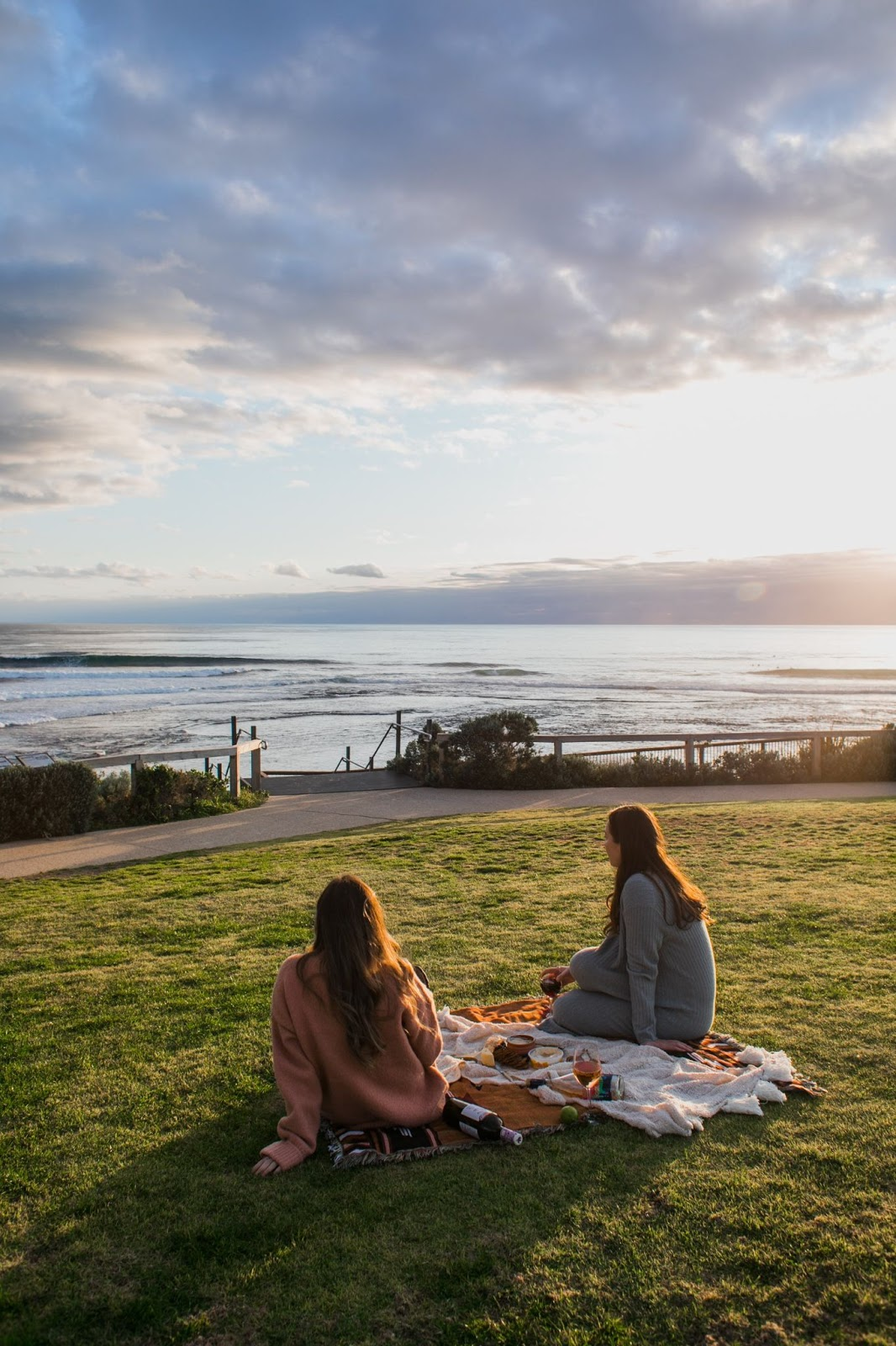 Two girls sitting on a picnic blanket looking out at the lake sunset.