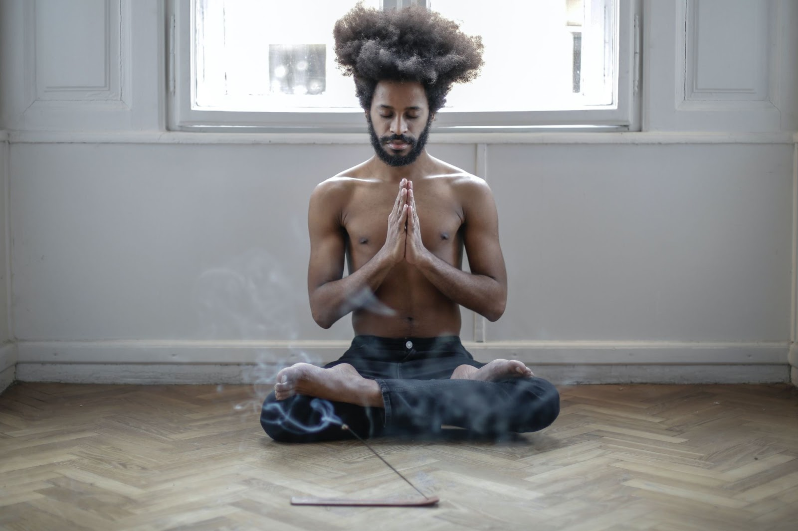 Man in a clear space sitting in the meditative position with his eyes closed.