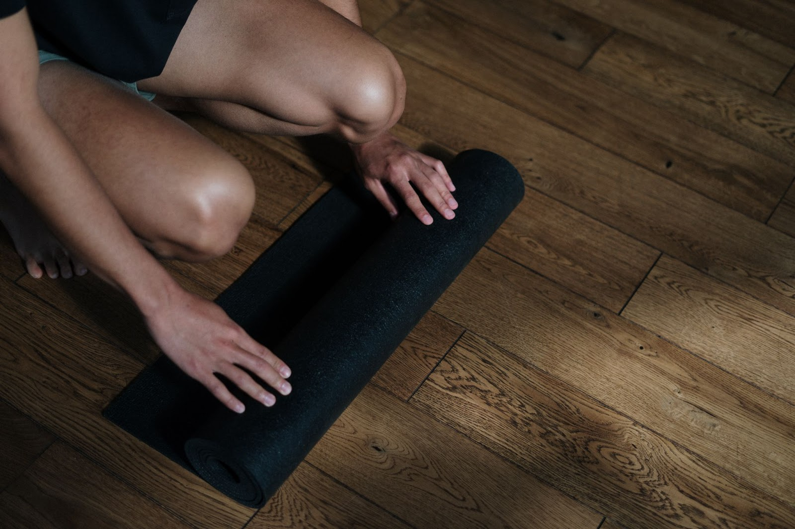 Person rolling out a yoga mat.