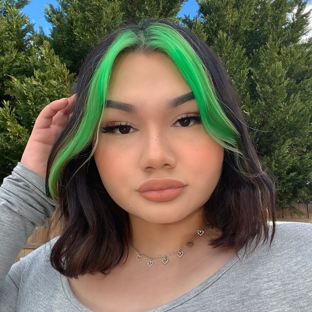 Young woman's face with black hair and neon green highlights in the front.