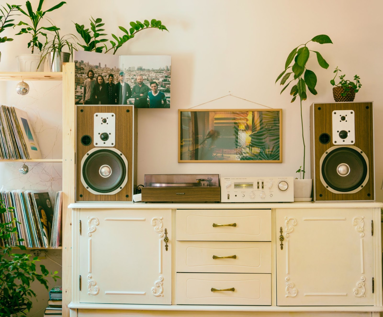 Entertainment center with boom boxes and potted plants as decoration around it.,