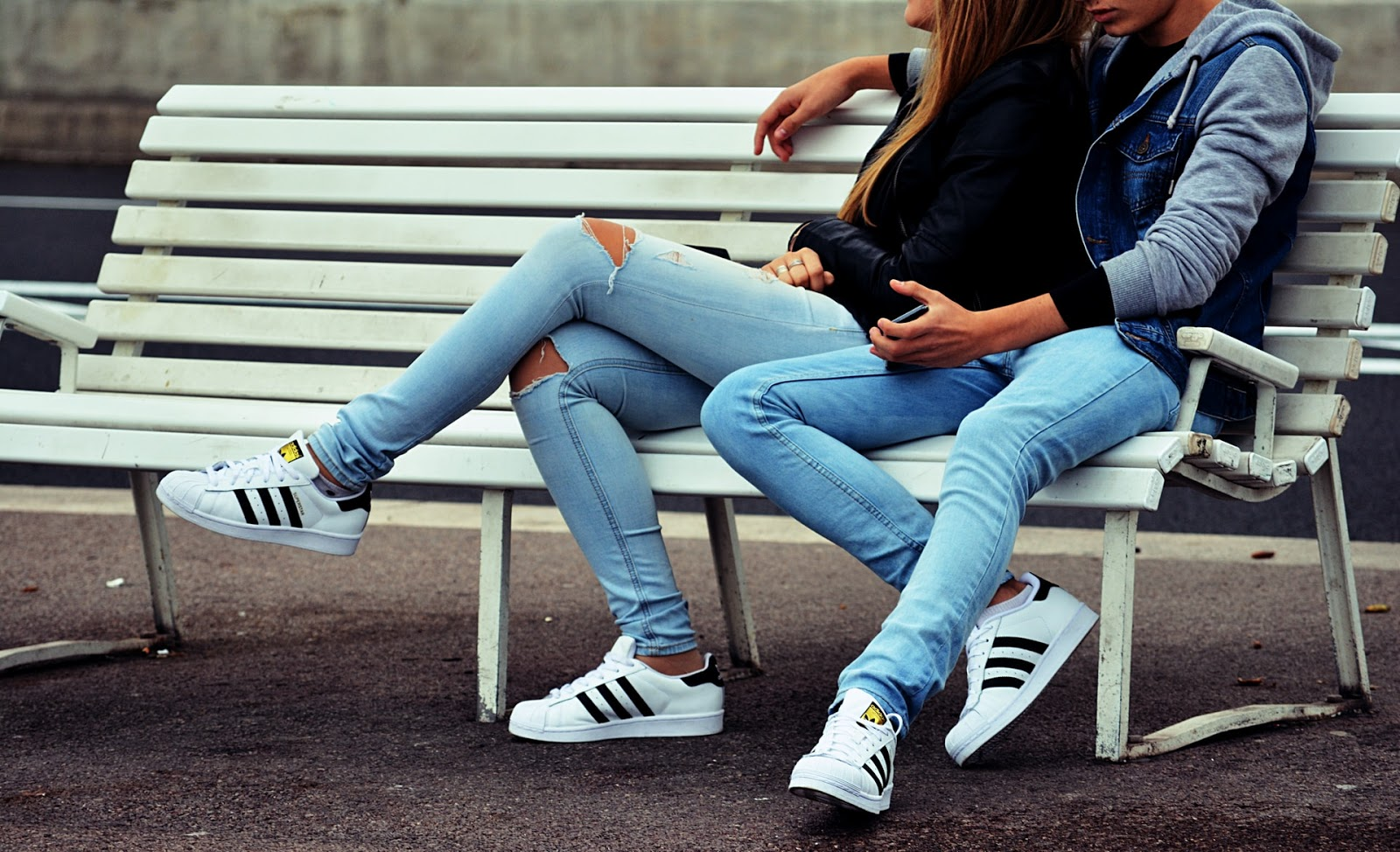 A couple sitting on a bench.