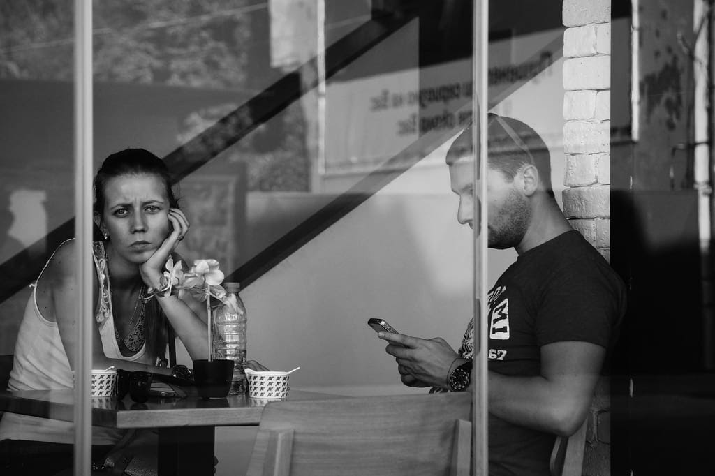 A woman looking into the window while being ignored.